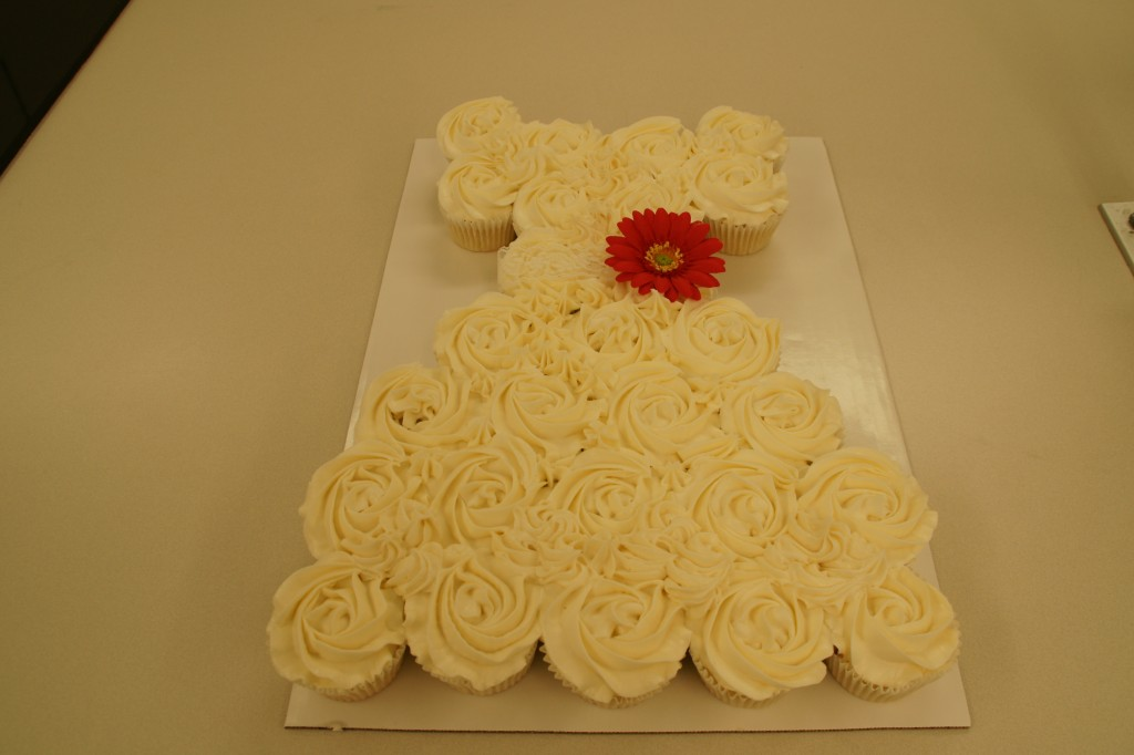 Thirty cupcakes are decorated with a rose tip and arranged to make a wedding dress.