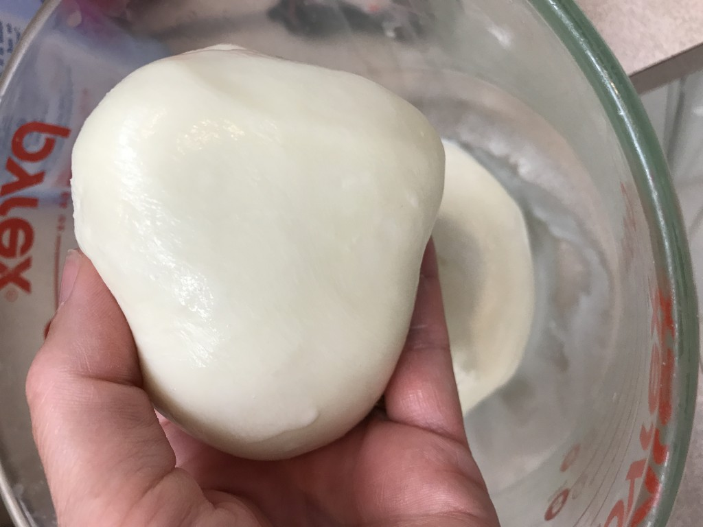 The fresh mozzarella ball is warmed, stretched and becomes a beautiful, smooth ball. It is ready to slice and serve.
