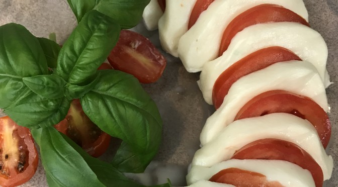 Tomatoes and basil make a stunning platter that showcases the most amazing cheese.